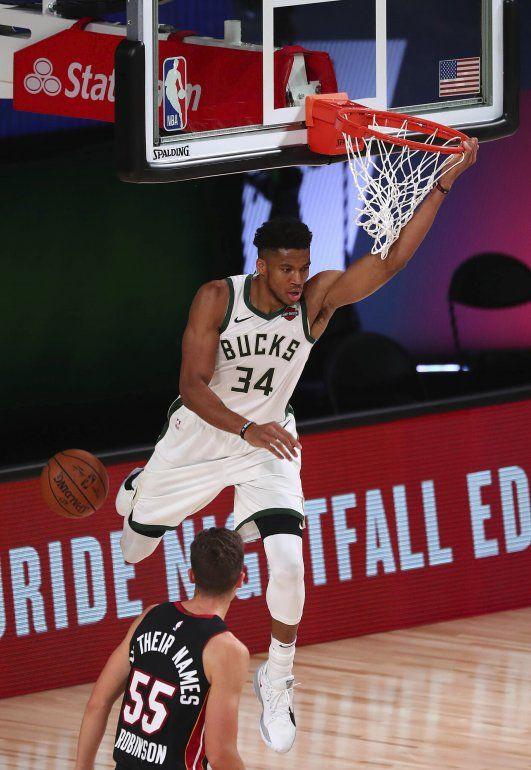 El alero de los Bucks de Milwaukee Giannis Antetokounmpo anota frente al base del Heat de Miami Duncan Robinson en el triunfo de su equipo 130-116 del jueves 6 de agosto del 2020 en Lake Buena Vista