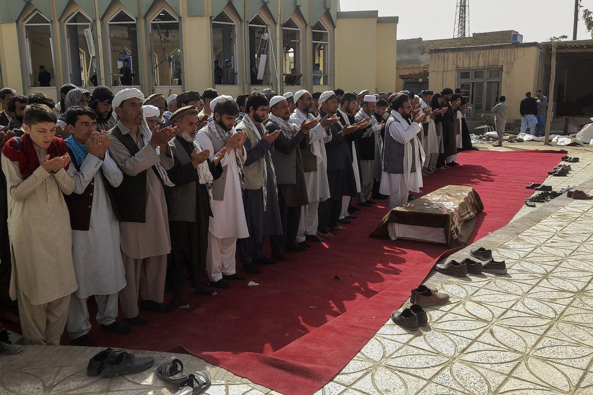 Familiares y residentes rezan durante el entierro de las víctimas de un ataque suicida en la mezquita de Gozar-e-Sayed Abad, en Kunduz, en el norte de Afganistán, el 9 de octubre de 2021.