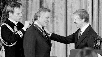 En esta fotografía de archivo del 16 de enero de 1981, el presidente Jimmy Carter, derecha, felicita al actor Kirk Douglas después de que recibió la Medalla de la Libertad, el mayor galardón para un civil en Estados Unidos, en la Casa Blanca en Washington.