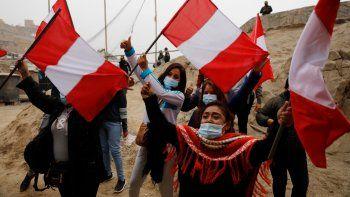 Los partidarios de la candidata presidencial Keiko Fujimori ondean banderas peruanas esperando su llegada a un desayuno en el barrio de San Juan de Lurigancho en Lima, Perú, el domingo 6 de junio de 2021