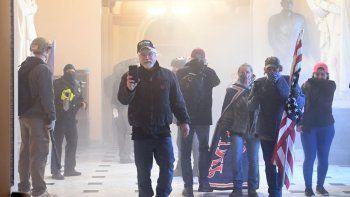 Partidarios del presidente de los Estados Unidos, Donald Trump, ingresan al Capitolio de los Estados Unidos mientras el gas lacrimógeno llena uno de los corredores de ese edificio, el 6 de enero de 2021, en Washington, DC. Los manifestantes violaron la seguridad y entraron al Capitolio mientras el Congreso debatía la Certificación de Voto Electoral para las elecciones presidenciales de 2020.