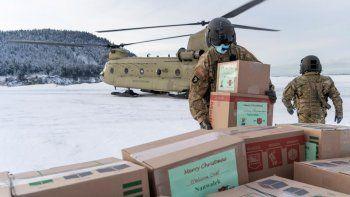 En esta fotografía facilitada por la Guardia Nacional de Alaska, soldados descargan regalos de un helicóptero CH-47 Chinook en Nanwalek, Alaska, durante la llamada Operación Santa Claus, el viernes 11 de diciembre de 2020.