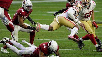 Jerick McKinnon, corredor de los 49ers de San Francisco, es derribado por Isaiah Simmons (48), linebacker de los Cardinals de Arizona, en el partido dle sábado 26 de diciembre de 2020, en Glendale.