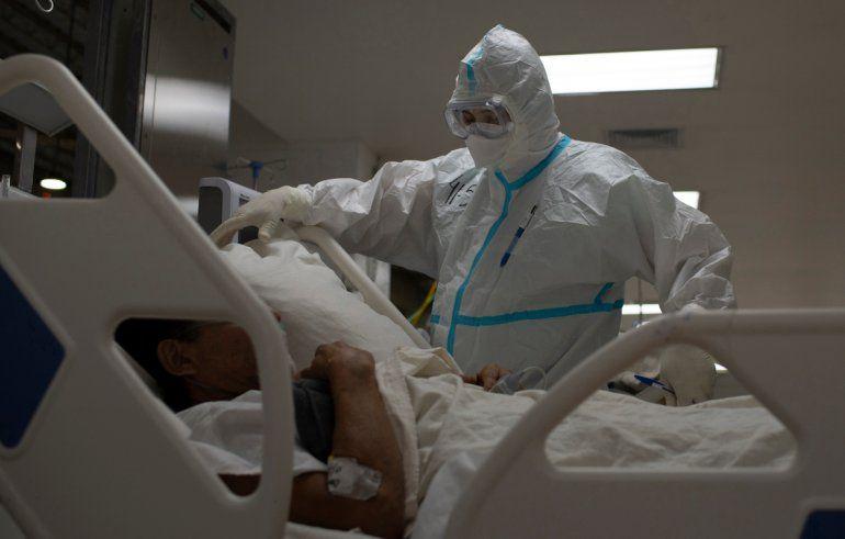 Un trabajador sanitario español y voluntario de la Fundación SAMU atiende a un paciente salvadoreño que sufre una crisis respiratoria por el nuevo coronavirus