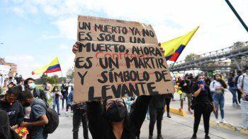 Una mujer sostiene un cartel que dice Un muerto ya no es solo un muerto, ahora es un mártir y un símbolo de levantamiento durante una manifestación contra la reforma tributaria propuesta por el presidente colombiano Iván Duque, en Bogotá, Colombia, en abril. 28 de 2021