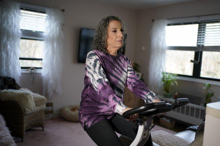 Catherine Busa se ejercita en una bicicleta estática en su casa de Nueva York el 13 de enero del 2021. Busa contrajo el COVID-19 y sobrevivió