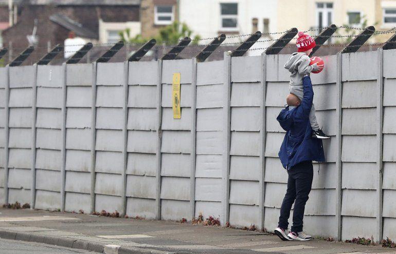 Un hombre sostiene a un niño para observar los entrenamientos del Liverpool en el centro de entrenamiento de Melwood. Encuentran seis casos de coronavirus en la primera ola de pruebas que se hicieron a jugadores y personal de 19 equipos de la Liga Premier de Inglaterra que regresa a entrenar con medidas de distanciamiento social el 19 de mayo del 2020.