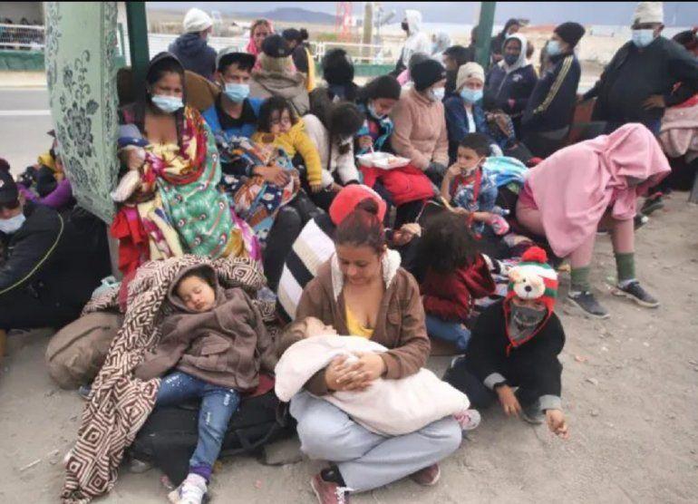 Los migrantes venezolanos, donde hay mujeres y niños, se reúnen después de cruzar ilegalmente la frontera entre Bolivia y Chile en Colchane, Chile, el 3 de febrero de 2021.