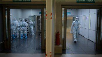 Los trabajadores médicos que usan equipos de protección personal, trabajan en un hospital temporal para pacientes con coronavirus establecido en Moscú.