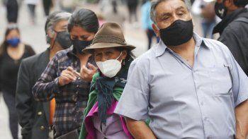 En esta fotografía de archivo del 8 de diciembre de 2020, los residentes con máscaras para frenar la propagación del nuevo coronavirus se alinean frente a un banco en Quito, Ecuador.
