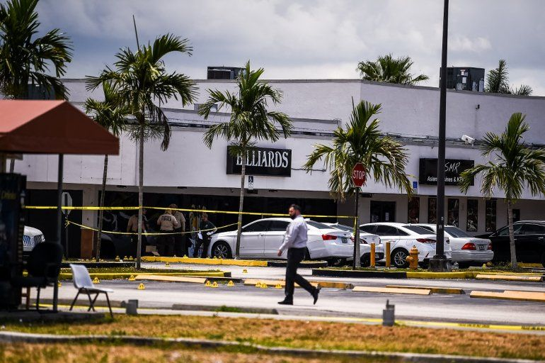 Agentes de la policía de Miami Dade recolectan evidencia del estacionamiento frente al club de Billar que fue alquilado para un concierto.