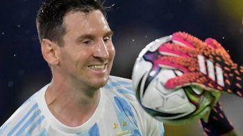 El arquero colombiano David Ospina atrapa el balón junto al argentino Lionel Messi durante un partido de clasificación sudamericano para la Copa Mundial de la FIFA Catar 2022 en el Estadio Metropolitano de Barranquilla.