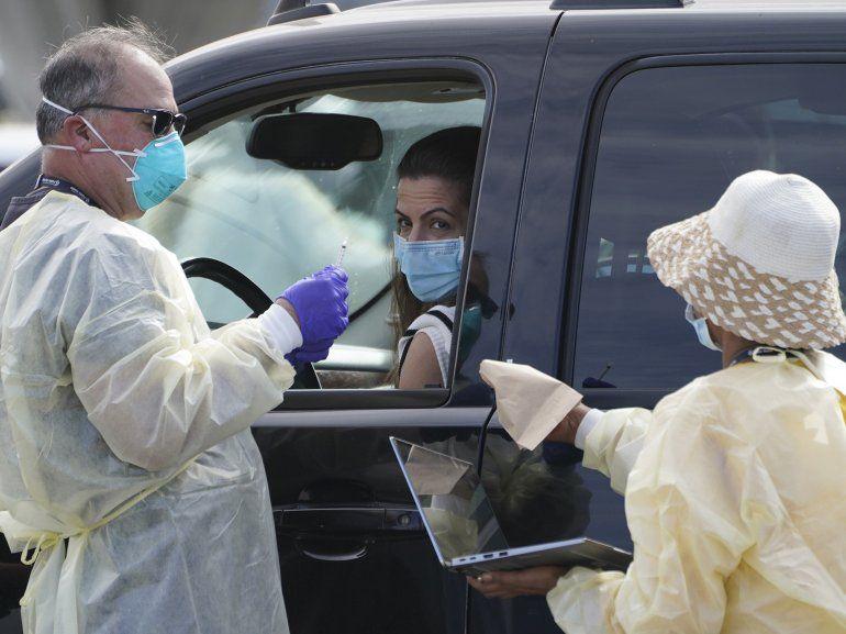 Personas hacen fila con sus vehículos en un centro de vacunación contra COVID-19 afuera de The Forum