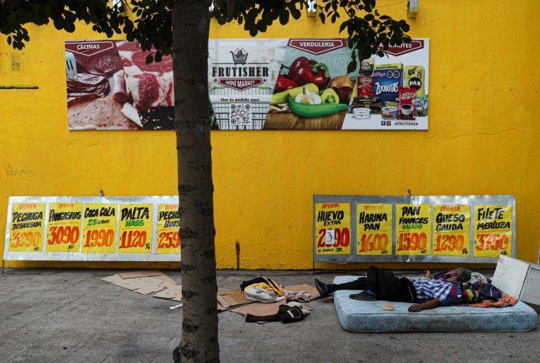 Un indigente duerme en un colchón en una acera cerca de una tienda de abarrotes en Santiago