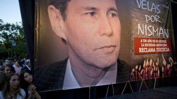 En esta foto de archivo del 18 de enero de 2016, mujeres se paran junto a una foto del difunto fiscal Alberto Nisman en el primer aniversario de su muerte en Buenos Aires, Argentina. Una miniserie documental de Netflix examina la sospechosa muerte de Nisman.