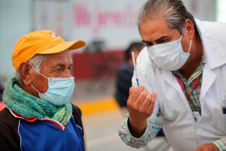 Uno de los enfermeros mexicanos muestra a un anciano una jeringa preparada con una dosis de la vacuna de Sinovac contra el coronavirus antes de aplicársela en el puesto de inoculación instalado en el Centro Cultural y Deportivo Las Américas