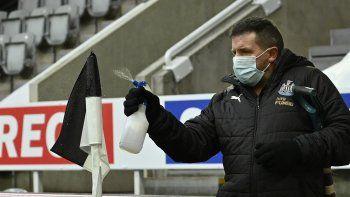 Un empleado rocía desinfectante la bandera de córner previo al partido de la Liga Premier inglesa entre Newcastle y Leicester City en el estadio St. James Park en Newcastle, el domingo 3 de enero de 2021.