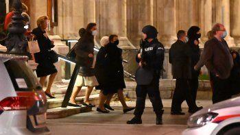 Los invitados a la ópera abandonan la ópera estatal bajo la supervisión de policías armados, en el centro de Viena el 2 de noviembre de 2020, luego de un tiroteo. Dos personas, incluido un atacante, murieron en un tiroteo en el centro de Viena, dijo la policía.
