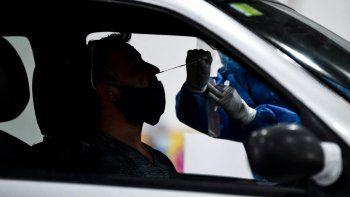 Un trabajador de salud recolecta muestras para la prueba de detección de casos de coronavirus COVID-19 dentro de un automóvil, en el centro de convenciones Costa Salguero, en Buenos Aires, el 5 de abril de 2021. El centro de convenciones se convirtió en un centro de pruebas de COVID para personas después de regresar de vacaciones. Argentina, con una población de 45,4 millones, tiene casi 2,4 millones de casos de covid-19, con más de 56.000 muertes.