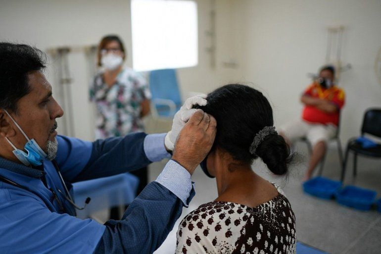 Trabajadores de la salud ayudan a recuperarse a pacientes venezolanos que tuvieron COVID-19 en el centro de salud administrado por el régimen en el barrio Coche de Caracas