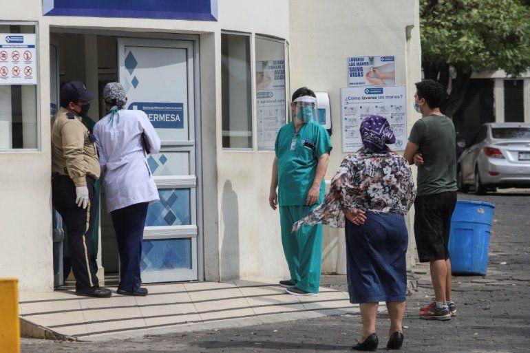 Un trabajador médico usa una máscara y un protector facial en la entrada del hospital SERMESA en Managua