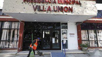 Un trabajador limpia la callefrente al ayuntamiento del pueblo de Villa Unión, México, tras un tiroteo que lo dejó lleno de agujeros de bala, el lunes 2 de diciembre del 2019.