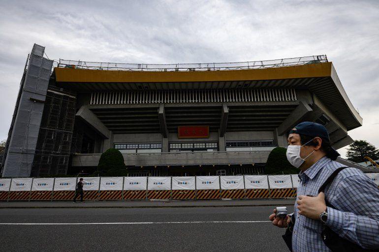 Un hombre usa una mascarilla mientras caminafrente a las obras en construcción del Estadio Nacional de Japón