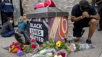 Varias personas se reúnen alrededor de un memorial improvisadopara honrar a George Floyd, el hombre afroestadounidense que murió asfixiado durante una operación de arresto policial en Minneapolis.