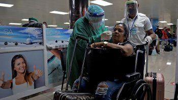 El personal de salud cubano recoge una muestra con hisopo para una prueba de COVID-19 a un pasajero en silla de ruedas en el Aeropuerto Internacional José Martí. Cuba estableció una tarifa de 30 dólares para todos los viajeros y tripulantes que lleguen a la isla por los servicios de control sanitario internacional.