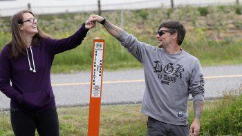 Kris Browning (izq) y su esposo Tim Browning se dan la mano por sobre un poste que marca el límite entre EEUU y Candá cerca de Lynden, Washington, el 17 de mayo del 2020.