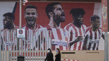 En esta foto del 5 de mayo de 2020, dos mujeres con mascarillas pasan frente a un afiche gigante con la imagen de jugadores del Atlético de Madrid en el estadio Wanda Metropolitano.