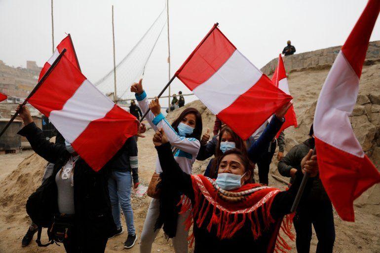 Los partidarios de la candidata presidencial Keiko Fujimori ondean banderas peruanas esperando su llegada a un desayuno en el barrio de San Juan de Lurigancho en Lima