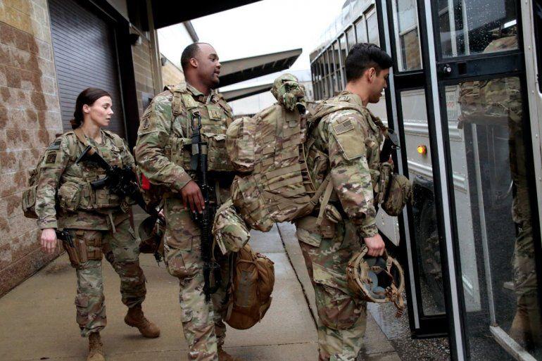 Soldados estadounidenses con su equipo suben a un autobús en Fort Bragg
