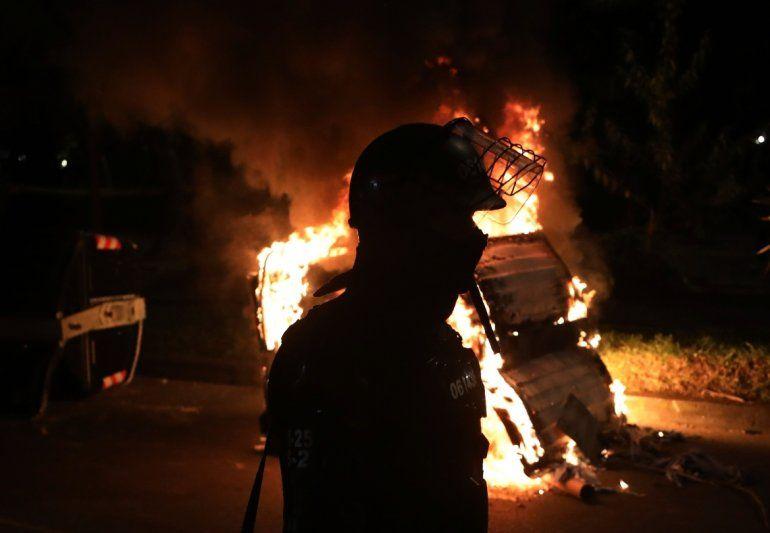 Un agente antimotines está parado detrás de una barricada en llamas durante las protestas por la muerte de un hombre a manos de la policía que lo detuvo por violar el distanciamiento social
