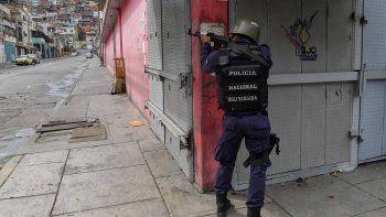 Un miembro de la Policía Nacional Bolivariana apunta a un posible objetivo luego de enfrentamientos con presuntos miembros de una banda criminal en el barrio Cota 905, en Caracas, el 9 de julio de 2021