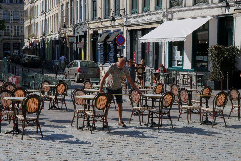 En dueño de un café mide la distancia entre las meses para respetar las normas de distanciamiento social en Lille