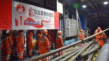 En esta imagen publicada por la agenica de noticias Xinhua, trabajadores de rescate junto a un cartel que dice El hogar es servir a tu región a la entrada de una mina de carbón inundada, en el condado de Hutubi, en la Prefectura Autónoma Hui de Changji, en el noroeste de la Región Autónoma Uigur de Xinjiang, China, el domingo 11 de abril de 2021. Varios mineros quedaron atrapados el sábado por una inundación subterránea, según medios.