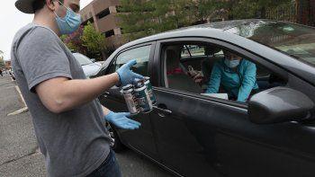 En esta foto del 8 de mayo del 2020, el empleado de la microcervecería Jacks Abby Casey Mott le lleva un pedido a un cliente en una fila de autos a la espera en Framingham, Massachusetts.