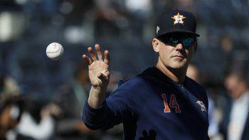En imagen de archivo del 15 de octubre de 2019, el mánager de los Astros de Houston AJ Hinch atrapa una pelota antes del tercer partido de la serie por el campeonato de la Liga Americana ante los Yanquis, en Nueva York.