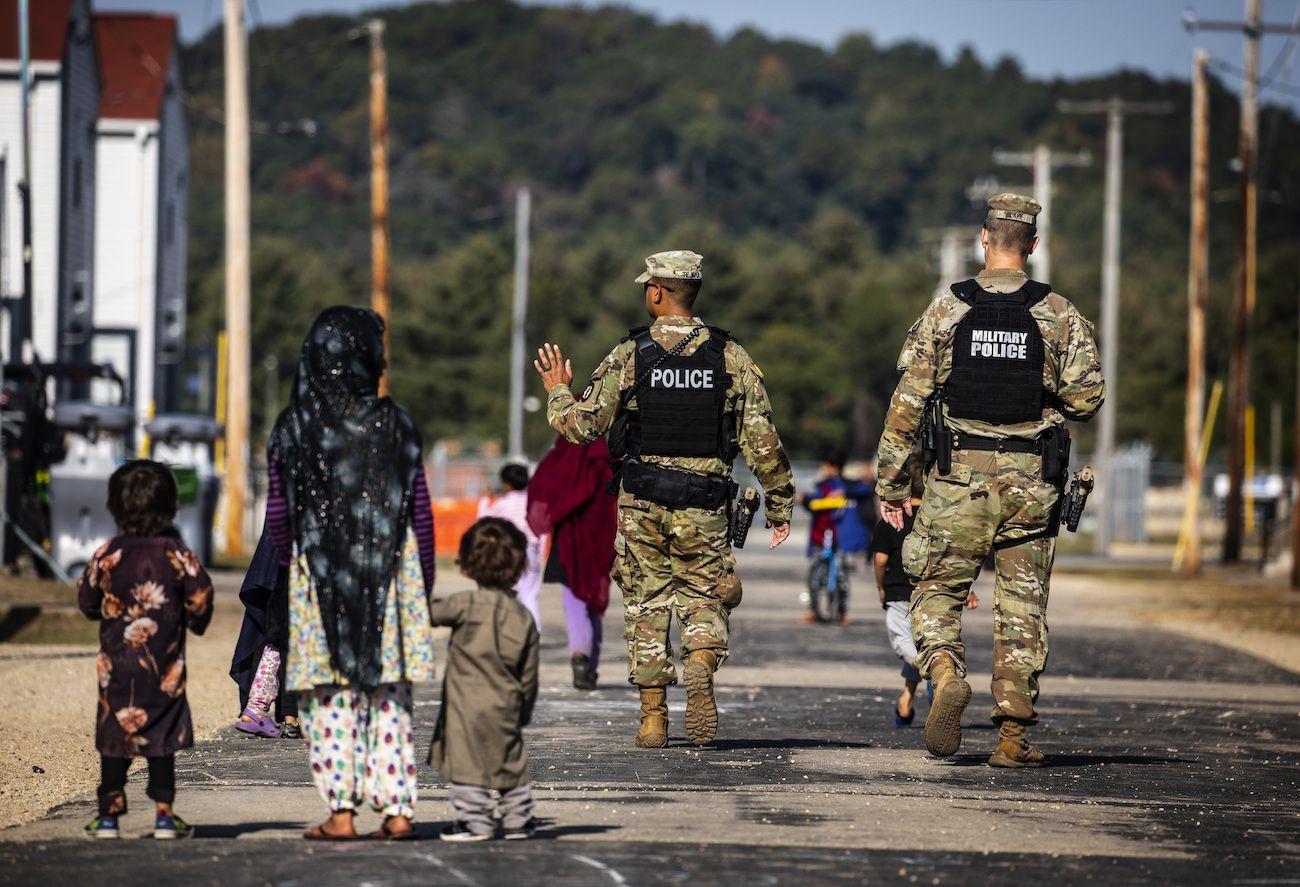 Policías militares caminan frente a unos refugiados afganos en la base del ejército estadounidense Fort McCoy, el jueves 30 de septiembre de 2021, en Fort McCoy, Wisconsin.