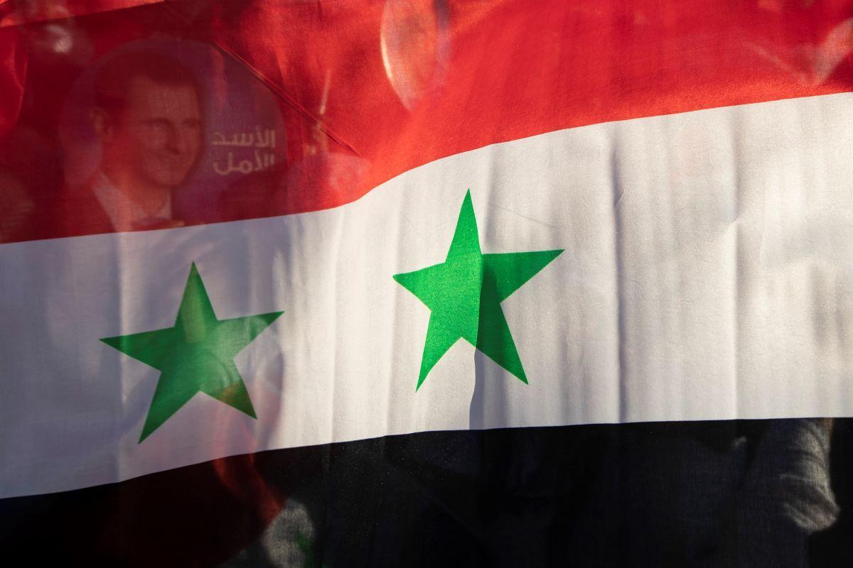 La bandera nacional de Siria, desplegada en una concentración en la Plaza Omayyid de la capital, Damasco.