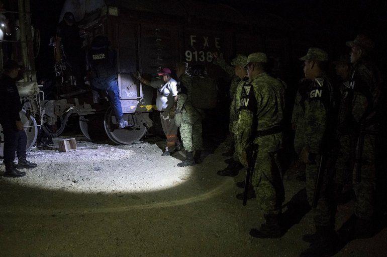 Efectivos de la nueva Guardia Nacional detienen a migrantes que viajaban de polizones en lo alto de los vagones del tren de carga conocido como La Bestia en la localidad de San Mateo