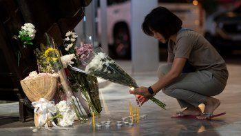Una mujer enciende una vela en el centro comercial Terminal 21 Korat, en Tailandia, después de una balacera que dejó al menos 29 muertos, el domingo 9 de febrero de 2020.