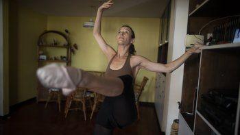 Carolina Wolf, bailarina de la compañía de ballet del Teatro Teresa Carreño, entrena en la sala de su casa en Caracas durante la cuarentena por la pandemia del coronavirus el martes 11 de agosto del 2020.