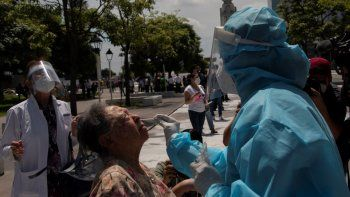 Un trabajador de salud realiza pruebas gratuitas de COVID-19 en una cabina móvil, en la plaza El Salvador del Mundo, en San Salvador, el 27 de julio de 2020.