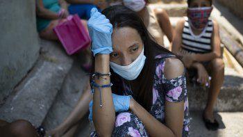 Una mujer, con mascarilla y guantes para protegerse del coronavirus, espera en el exterior de un comedor benéfico gestionado por monjas para recibir algo de comida, en la barriada de Petare, en Caracas, Venezuela, el 30 de abril de 2020.