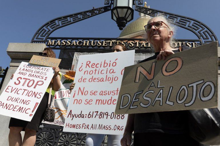 Personas de una coalición por la justicia en las viviendas llevan carteles de protesta contra los desalojos durante una conferencia de prensa junto a la legislatura de Massachusetts