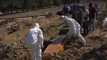 Empleados de un cementerio con trajes especiales para protegerse del coronavirus entierran el miércoles 20 de mayo de 2020 a Amanda da Silva, de 22 años, que falleció de COVID-19, en el cementerio de Caju, en Río de Janeiro.