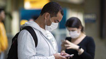 Pasajeros usando mascarillas como precaución contra el contagio del nuevo coronavirus usan sus teléfonos en el Aeropuerto Internacional de Sao Paulo, Brasil, el jueves 27 de febrero de 2020.