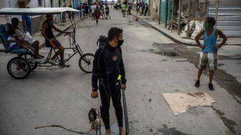 Con una máscara facial en medio de la pandemia del nuevo coronavirus, el buzo Yuniel González camina a casa con su pesca del día en La Habana, Cuba, el martes 27 de octubre de 2020.